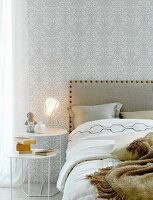 Double bed, white and silver pattern wallpaper and tan details