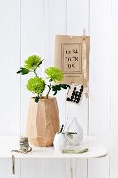 Three chrysanthemum 'Anastasia' flowers in mango-wood vase on white metal table; vintage items decorating wall
