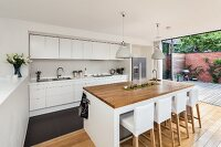 Bar stool with white loose covers at island counter in open-plan designer kitchen with open terrace doors to one side