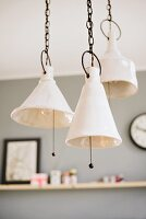 Artistic, ceramic pendant lamps hanging from chains with pull switches