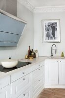 White fitted kitchen in period apartment with stucco frieze; cast iron pot on ceramic hob and historical black and white photo over sink