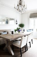 Comfortable dining area with chandelier above solid wood table and simple upholstered furnishings in kitchen-dining room