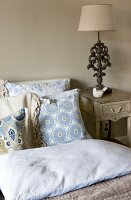 Table lamp with classic base on antique-style bedside cabinet next to pale blue patterned scatter cushions on bed
