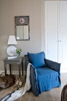 Lady's accessories next to blue, loose-covered armchair in bedroom next to lamp on table below mirror