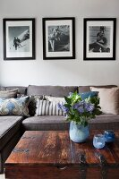 Retro black and white photos above sofa with collection of scatter cushions; vase of flowers and tealight holders in shades of blue on trunk table