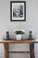 Black and white photo above candle lanterns and potted plant on rustic console table