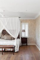 Bedroom with canopy, antique furniture and leaf-patterned wallpaper