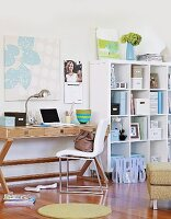 White, pastel blue and green colour scheme in inviting home office with wooden desk and storage shelves decorated with photos and artworks