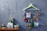 Hand-crafted Advent calender with small parcels hanging from coat hanger on wall