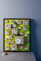 Hand-crafted Advent calendar with small parcels attached to picture frame with green background leaning against wall