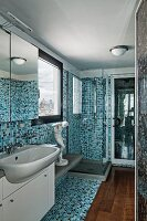 Narrow bathroom with mosaic tiles in various shades of blue, white washstand with mirrored cabinet and wooden floor section