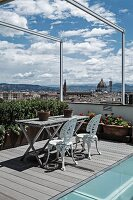 Seating area with vintage metal chairs painted white and weathered wooden table on roof terrace with view across Florence