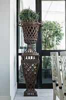 Planter on rusty, metal lattice plinth in loggia-style room