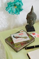 Detail of desk - old cigar tin next to metal bust of Buddha and turquoise silk flower on wall