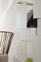 Modern shelving with white screens behind fifties-style armchair