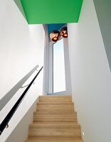 Pale wooden staircase with black handrail in narrow stairwell with copper-coloured pendant lamps over landing and green-painted ceiling