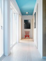 Light-flooded hallway with pale wooden floor, red chair below picture on end wall and spotlight on ceiling painted light blue