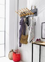 A homemade coat rack made from wooden hangers mounted onto a wooden board next to a narrow wall table against a whitewashed brick wall