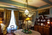 Historic house in Burgundy - dining room with blue and white wood panelling and elegant furnishings