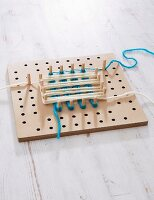 A pegboard with different coloured wool wrapped around the pegs