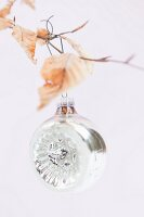 Silver Christmas bauble hanging from birch twig with dry leaves