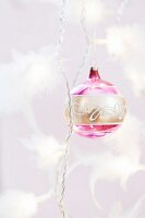 Gold and pink Christmas baubles on twisted cord decorated with feathers