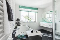 A modern, black and white bathroom with a bubble-jet bathtub and a chrome-plated laundry box stool in front of it with a double washstand in the background