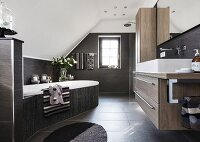 An elegant designer bathroom under a vaulted roof in various brown tones with a bathtub at an angle in the room