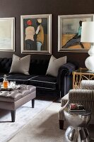 Ottoman, elegant black sofa with grey scatter cushions, framed pictures on black-painted wall