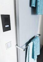 A flat panel radiator with a towel rail next to a built-in radio and lighting controls
