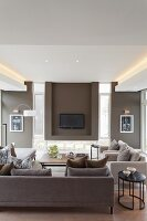 Elegant sofa set in various shades of brown, flatscreen TV on wall in niche flanked by narrow vertical windows and indirect lighting from ceiling