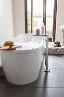 A free-standing bathtub in front of a balcony door with a floor tap on a slate floor