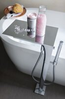 A chrome-plated floor tap with a waterfall spout and a shelf of bathing utensils
