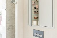 A small cupboard built into a wall niche with an open door and a view of bathroom utensils