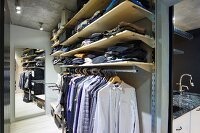 Dressing room with open-fronted wardrobe system; shirts hanging on rack below shelves