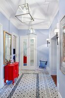 Hallway with patterned tiled floor, pale blue walls and red, postmodern chest of drawers