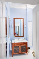 View though open door into bathroom with mahogany-coloured, wooden washstand against wall painted pale blue