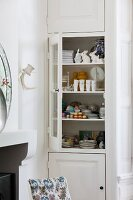 Jumble of crockery and china ornaments in fitted cupboard with open glass door