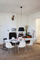 Black pendant lamp above white, oval dining table and shell chairs; fireplace and workspace in background