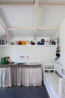 Watering cans and kitchen utensils on shelf under sloping ceiling above sink unit with curtain; old storage bench to one side