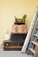 Vintage-style still-life arrangement on tray and rabbit ornament on stack of crates and suitcases next to carved wooden pillar and old ladder