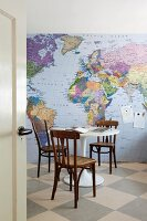 Old, bentwood chairs and office utensils on white Tulip table in front of wallpaper mural showing map of the world