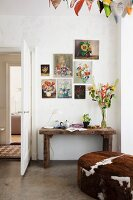 Collection of classic, floral, still-life paintings above rustic console table and pouffe with animal-skin cover below garland of fabric love-hearts