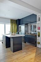 Modern, grey fitted kitchen with free-standing sink unit and ornaments on fitted shelves in frame of wide, open doorway