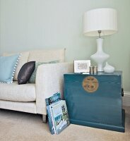 Elegant white table lamp on Oriental-style trunk painted blue-grey next to modern couch with pale linen cover against pastel wall