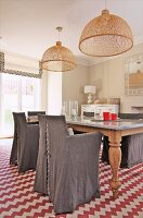 Chairs with grey loose covers around dining table below wicker pendant lamps and rug with red and white zigzag patterns in country-house interior