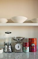White china bowls on floating shelf and colourful Chinese tea caddies next to retro kitchen appliances on marble counter