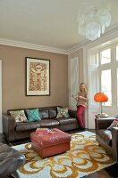 Pink, leather ottoman on patterned rug and woman standing next to brown, leather sofa in traditional interior