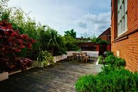 Bushes and palm trees in raised beds surrounding wooden terrace with table and benches adjoining brick facade of converted church