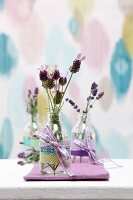 Sprigs of lavender in glass bottles decorated with ribbons and washi tape decorating table